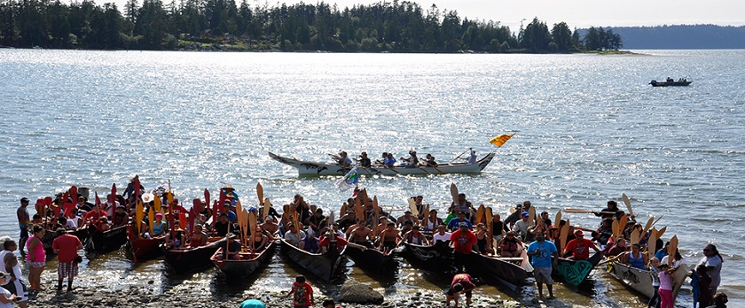 People enjoying a canoe journey landing on a beautiful day at Tulalip Bay